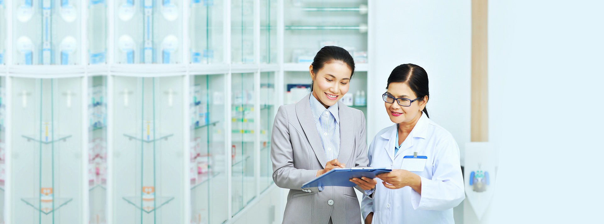 business woman showing document to a pharmacist