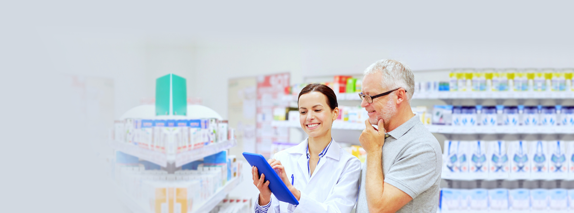pharmacist and customer looking a tablet