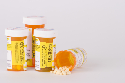 group of four prescription medication pill bottles with one open and small pills spilling out