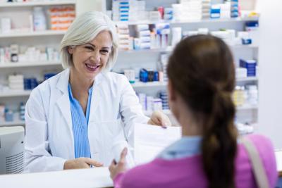pharmacist giving prescriptions of medicine to customer