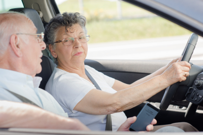 elderly lady driving, husband talking to her